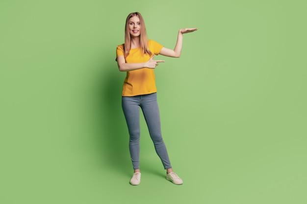 Portret van betrouwbare dameshand toont lege ruimte, directe vinger draagt geel t-shirt geïsoleerd op groene kleur achtergrond