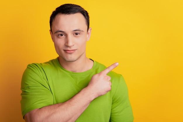 Portret van betrouwbare positieve man directe wijsvinger lege ruimte op gele achtergrond