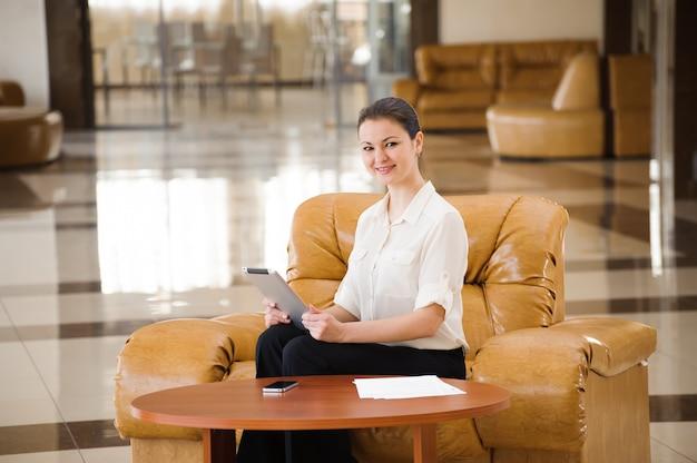 Portret van bezige bedrijfsvrouw die aan ipad werkt terwijl het zitten bij bank. klein bedrijf.