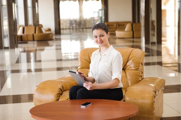 Portret van bezige bedrijfsvrouw die aan ipad werkt terwijl het zitten bij bank.