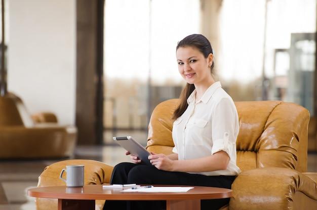 Portret van bezige bedrijfsvrouw die en bij bank werken zitten