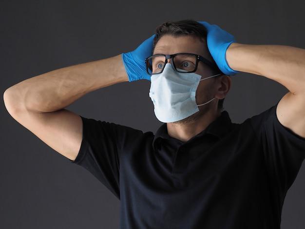 Portret van bezorgd persoon met chirurgische gezichtsmasker virusbescherming en handschoenen houden zijn hoofd in shock en paniek.