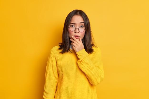 Portret van bezorgd verrast aziatische vrouw houdt kin kijkt bezorgd draagt transparante bril en trui.