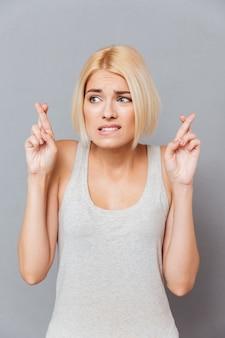 Portret van bezorgde angstige jonge vrouw met vingers gekruist over grijze muur