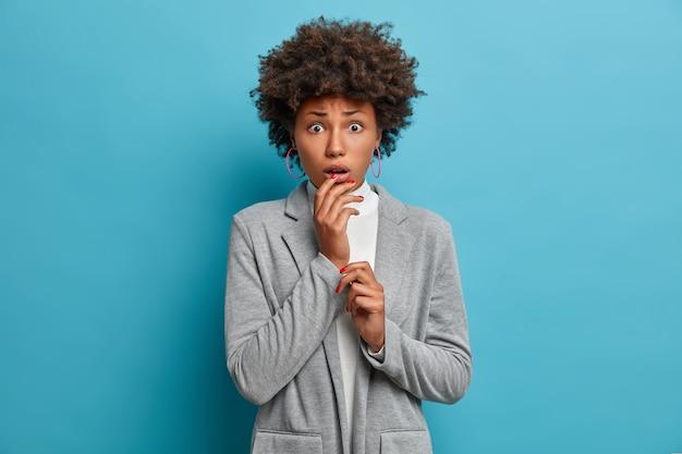 Portret van bezorgde bezorgde jonge afro-amerikaanse vrouw kijkt met schok en paniek, houdt hand in de buurt van geopende mond, angstig en bang