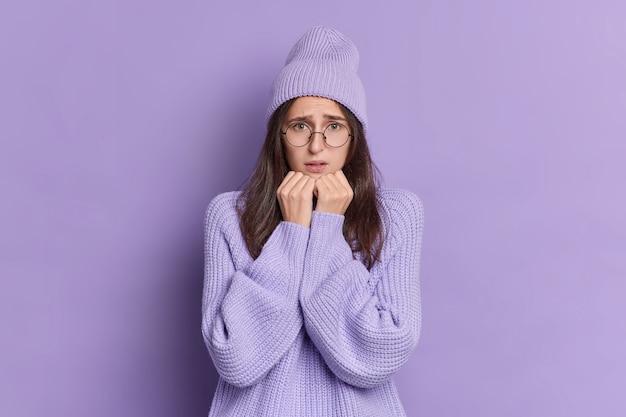 Portret van bezorgde brunette mooie vrouw houdt handen in de buurt van kin en beeft van angst voelt zenuwachtig heeft lange rechte donkere haren gekleed in gebreide paarse winter hoed trui. Gratis Foto