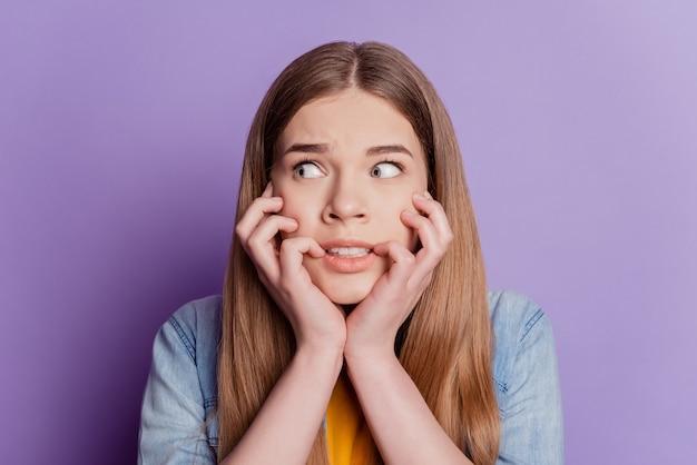 Portret van bezorgde dame bijt nagels angstig kijken lege ruimte draag jeans kleding op paarse achtergrond