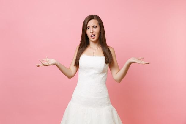 Portret van bezorgde overstuur vrouw in elegante kanten witte jurk die staat en handen spreidt