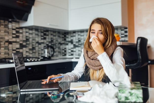 Portret van bezorgde zakenvrouw die servetten vasthoudt en niest in de keuken thuis en laptop gebruikt