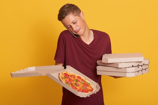 Portret van bezorger die via de telefoon spreekt, een bordeauxrood casual t-shirt draagt, dozen met pizza vasthoudt, krijgt een nieuwe bestelling via zijn smartphone