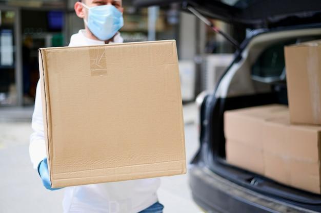 Portret van bezorger houden kartonnen doos