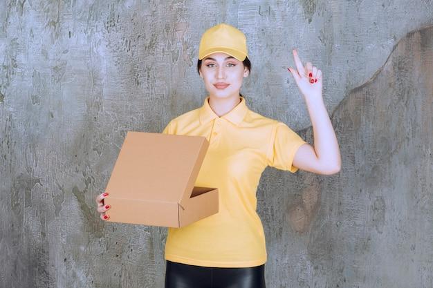 Portret van bezorger vrouw met kartonnen doos die omhoog wijst