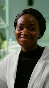 Portret van bioloog onderzoeker vrouw in witte jas op zoek naar camera