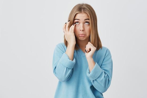 Portret van blanke jonge vrouw met ovaal gezicht, donkere ogen en blond steil haar, gekleed in een blauwe casual trui, haar gezicht aanraken, proberen wimper uit haar oog te krijgen, naar boven kijkend.