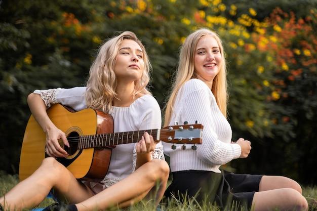 Portret van blanke jonge vrouwen die buiten in het park zitten en gitaar spelen, zingen samen met geluk een lied with