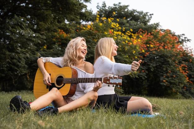 Portret van blanke jonge vrouwen die buiten in het park zitten en gitaar spelen, zingen samen met geluk een lied