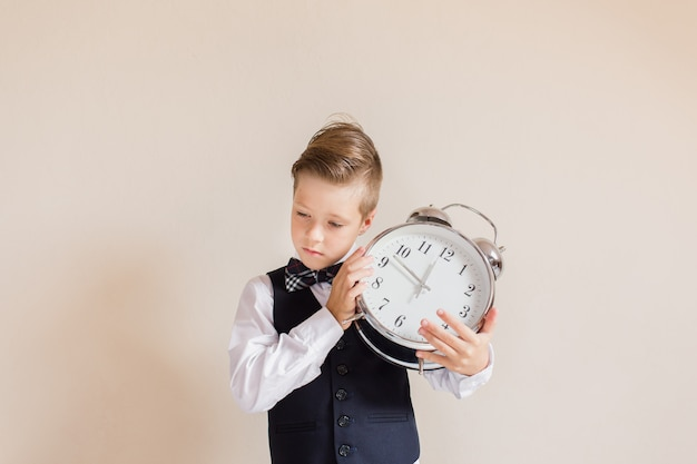Portret van blanke jongen in grijs pak met grote klok. leuke jongen houden en horen klok. kind terug naar school. onderwijs en tijd concept.
