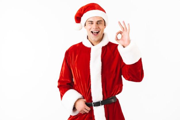 Portret van blanke man 30s in kerstman kostuum en rode hoed gebaren met glimlach