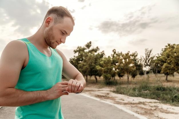 Portret van blanke man in azuurblauwe t-shirt kijken naar fitness tracker lezingen