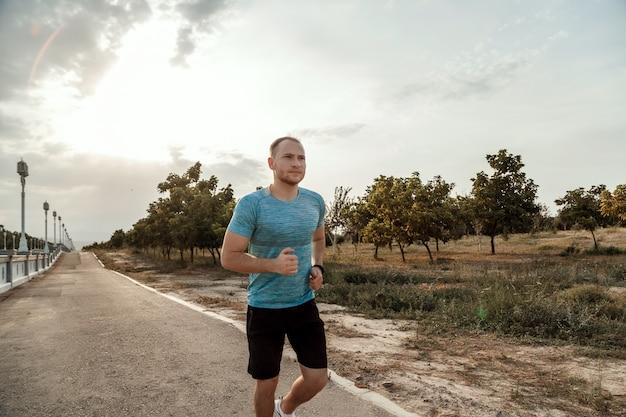 Portret van blanke man in een blauw t-shirt en zwarte korte broek die tijdens zonsondergang op het asfaltspoor traint en loopt
