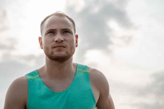 Portret van blanke man loopt over ruw terrein. training tijdens zonsondergang