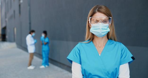 Portret van blanke mooie vrouw arts in medische masker en bril camera kijken. vrouwelijke arts in ademhalingsbescherming close-up. multi-etnische artsen op achtergrond. medic op het werk.