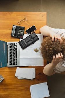 Portret van blanke ongeschikte en wanhoopsmens die op financiële en economische grafieken letten tijdens coronavirusquarantaine, problemen