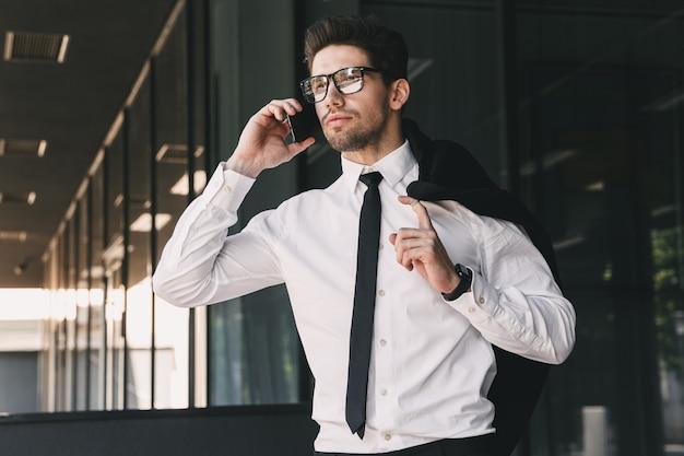 Portret van blanke zakenman gekleed in formeel pak staande buiten glazen gebouw met jasje over zijn schouder, en praten over de mobiele telefoon