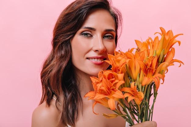 Portret van blauwogige vrouw met oranje bloemen in haar handen. foto van donkerharige meisje met mooie glimlach met groot boeket.