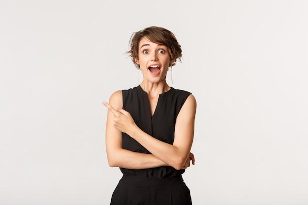 Portret van blij en verrast blanke vrouw met open mond gefascineerd, wijzende linkerbovenhoek op promobanner, wit.