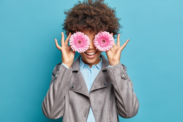 Portret van blij gekrulde jonge vrouw bedekt ogen met twee roze gerberabloemen heeft lentestemming glimlach gelukkig gekleed in overhemd en grijze jas geïsoleerd over blauwe muur vindt inspiratie