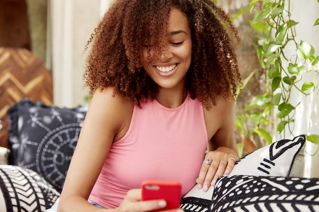 Portret van blij gemengd raced afro-amerikaanse vrouw installeert app op slimme telefoon, zit op de bank, updates profiel in sociale netwerken of berichten online op slimme telefoon, zit op comfortabele bank