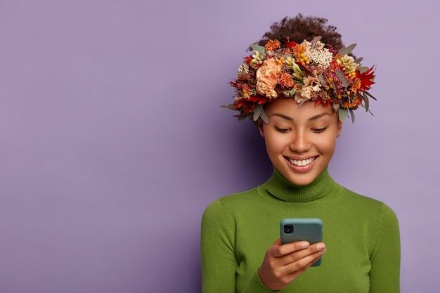 Portret van blij herfstmodel draagt decoratieve herfstkrans, gericht op smartphoneapparaat, leest goed nieuws online, heeft een blije gezichtsuitdrukking, modellen over paarse studiomuur.