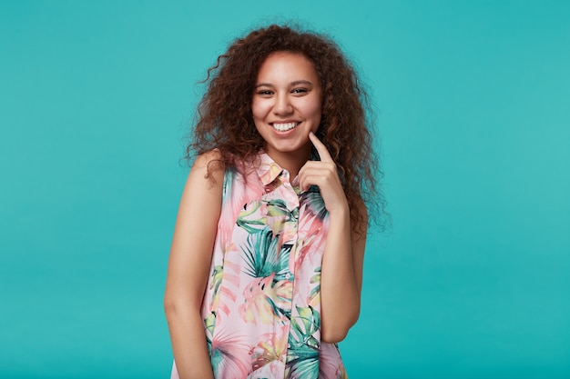 Portret van blij jong mooi bruinharig krullend wijfje dat wijd glimlacht en opgeheven wijsvinger op haar wang houdt, geïsoleerd op blauw