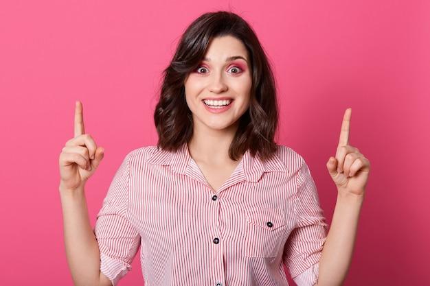 Portret van blij meisje dat gestreept overhemd draagt, direct camera bekijkt, wijzend beide wijsvingers omhoog, jonge vrouw met groot idee, die zich tegen roze muur bevindt.