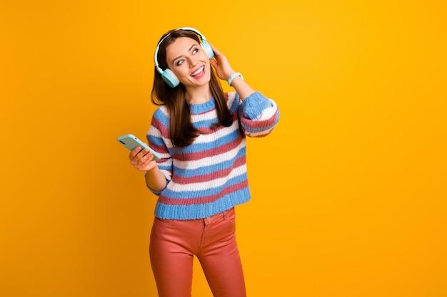 Portret van blij meisje luisteren muziek in koptelefoon opzoeken hold telefoon