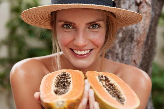Portret van blij mooie vrouw naakt vormt, draagt zomerhoed, houdt organische exotische papaja