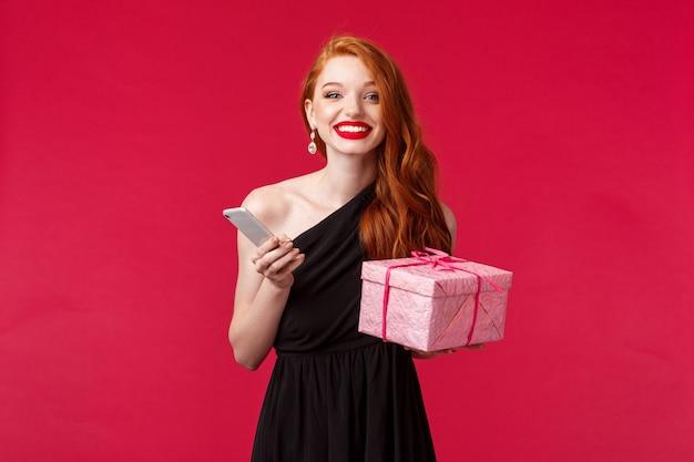 Portret van blij, opgewonden aantrekkelijke vrouw met gember haar, viert verjaardag, vakantie met cadeautjes, ontvang cadeau, houd doos en smartphone lachen glimlachen, rode muur