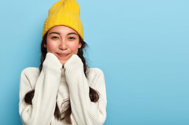 Portret van blij schattige aziatische vrouw houdt handen onder de kin, gekleed in oversized witte trui en gele hoed, geniet van comfort en rustige huiselijke sfeer