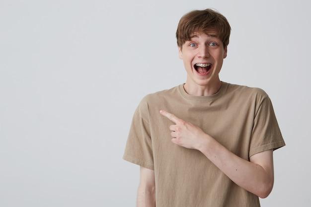 Portret van blij verrast jongeman student met metalen accolades op tanden en geopende mond in beige t-shirt