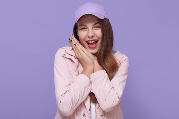 Portret van blij vol geluk meisje met wijd open mond en gelukkige ogen, handpalmen bij elkaar houden in de buurt van de wang