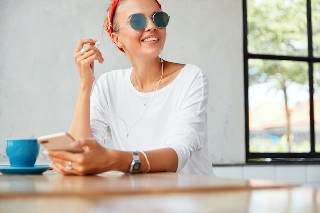 Portret van blij vrouwelijk model oortelefoons zet, geniet van perfecte lied of favoriete muziek, aangesloten op moderne mobiele telefoon, zit aan tafel met kopje koffie tegen café interieur. mensen en rust concept