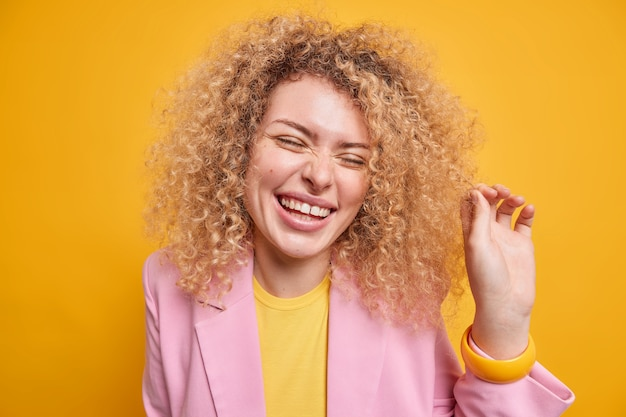 Portret van blije europese vrouw met krullend borstelig haar glimlacht vrolijk en drukt authentieke emoties uit, voelt zich erg blij sluit de ogen van plezier gekleed in elegante kleding geïsoleerd op gele muur