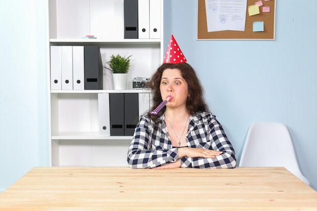 Portret van blije gelukkige jonge vrouw met grappige kegel op hoofd en genietend van verjaardagspartij, vakantieviering.