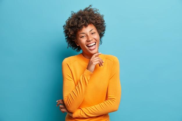 Portret van blije jonge vrouw lacht vrolijk houdt hand op kin drukt positieve emoties uit glimlacht in het algemeen heeft zorgeloze uitdrukking draagt oranje trui geïsoleerd over blauwe muur