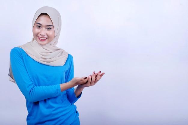 Portret van blije jonge vrouw met blauwe t-shirt die hijab draagt die iets toont