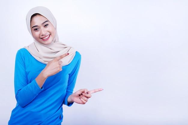 Portret van blije jonge vrouw met blauwe t-shirt die hijab draagt die rechterkant met twee wijsvingers richt
