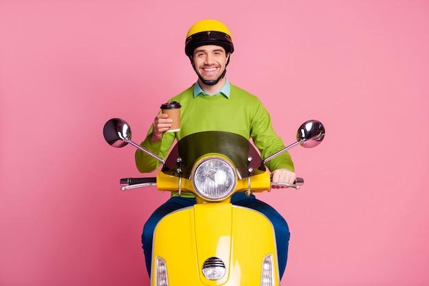 Portret van blije man zittend op bromfiets houden afhaalmaaltijden koffiekopje