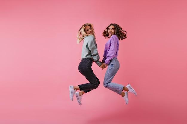 Portret van blithesome beste vrienden hand in hand op roze. charmante zusters in trendy broek springen en lachen.
