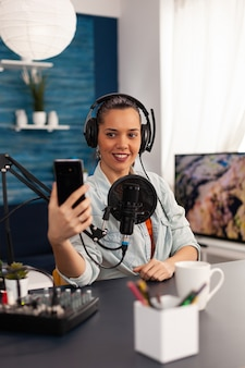 Portret van bloggervrouw die selfie voor publiek neemt met smartphone die in podcast-thuisstudio werkt. contentmaker die nieuwe mode- en beautyrecensies opneemt en plezier heeft op het sociale mediaplatform.